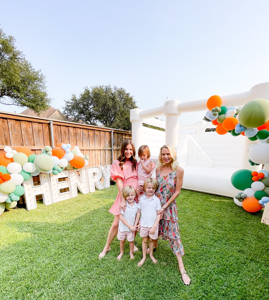 two women with three young boys in front of henry marquee lights and white bounce house with balloon garland