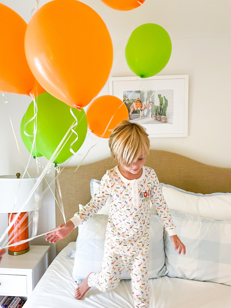 toddler boy jumping on bed with orange and green balloons
