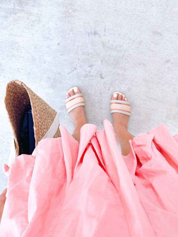 looking down at peach colored dress and striped shoes