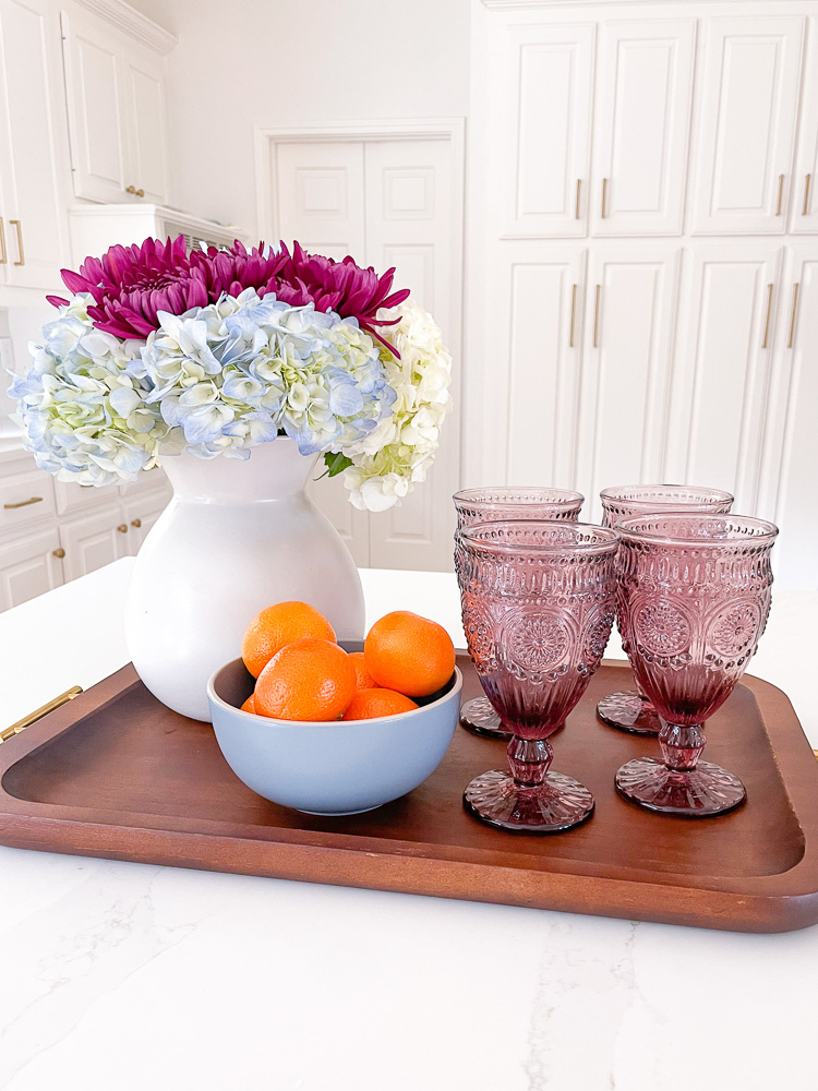 still life flowers in vase purple goblets and bowl of oranges