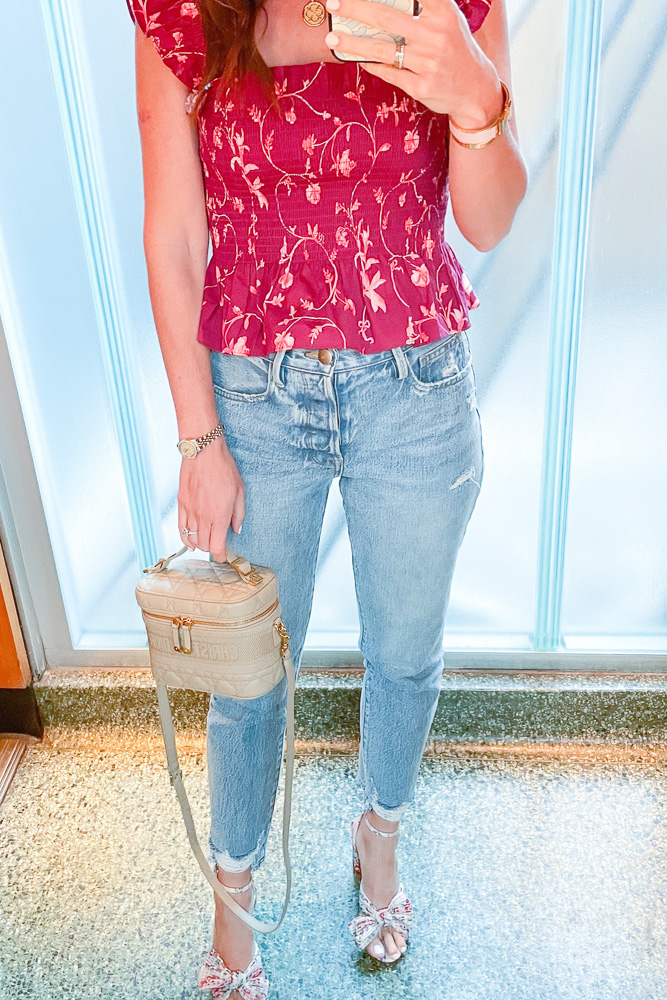 mirror selfie of woman in jeans and floral top
