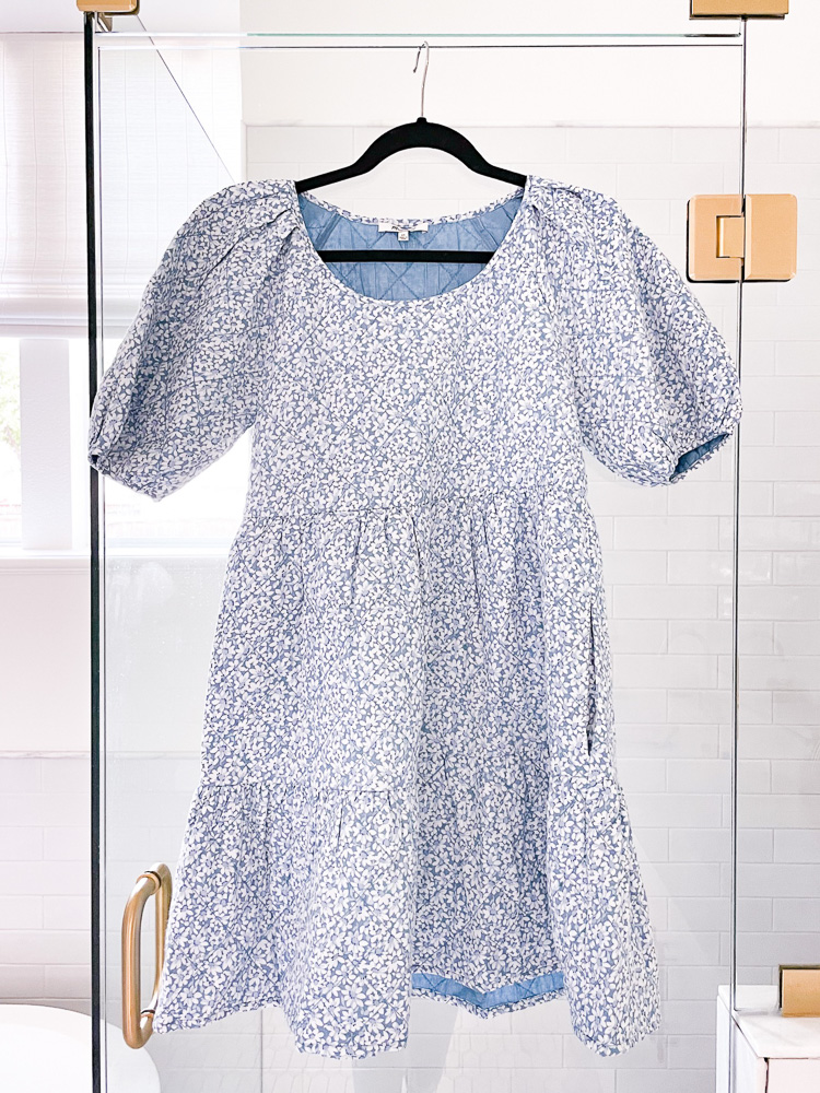 blue floral puff sleeve dress hanging on shower door