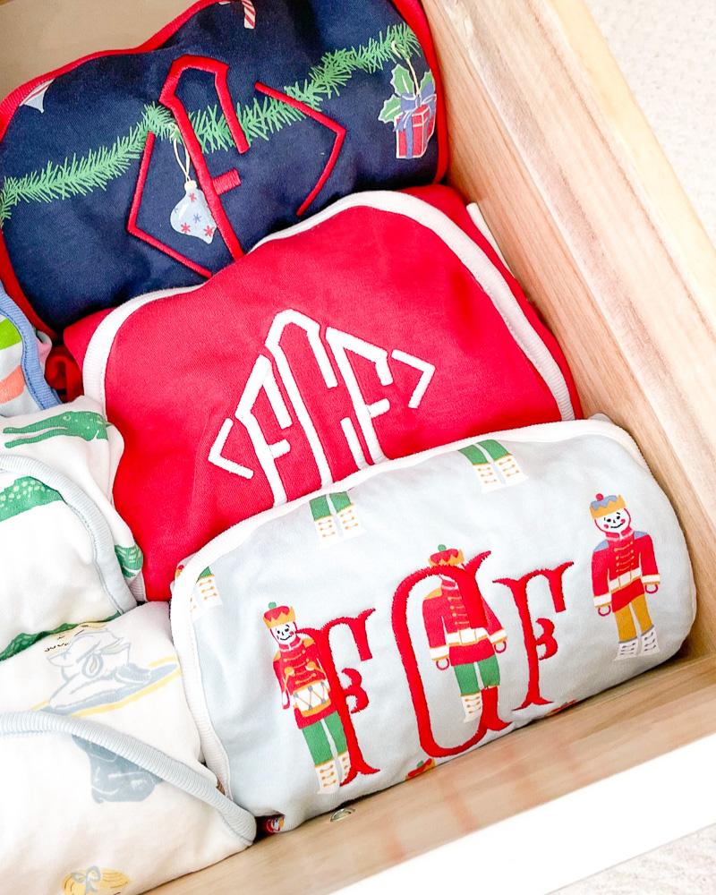 an assortment of folded kids christmas pajamas with monograms