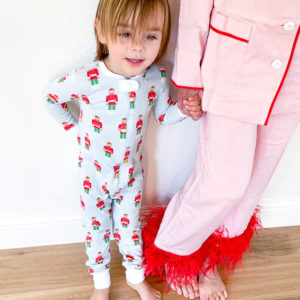 toddler boy in christmas pajamas holding hands with woman in pink pajama set with feather hem